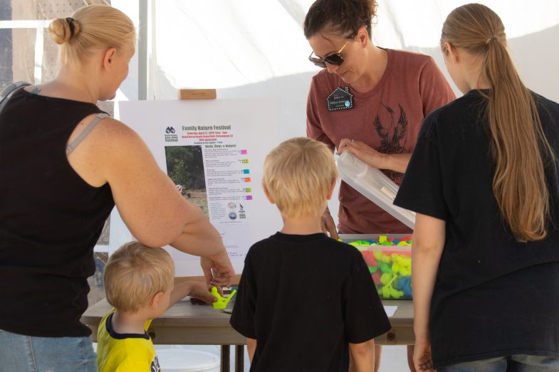 Children and family at the nature festival look at an activity